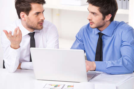 two businessmen having discussion in office. two businessmen looking at each other and using laptop photo