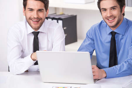 two businessmen having discussion in office. two smiling businessmen looking at camera with laptop photo