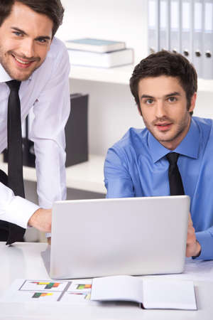 two businessmen having discussion in office. Two businessmen looking at camera and graphs on table photo