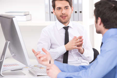 two businessmen having discussion in office. over shoulder view of businessmen looking at each other and using laptop Standard-Bild