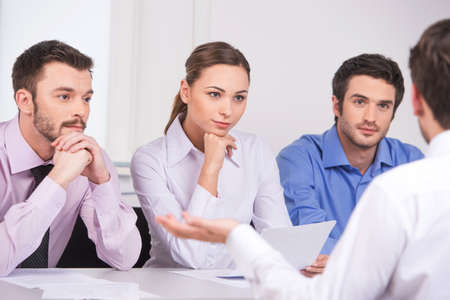 over the shoulder view: Group of young business people talking on business meeting. over shoulder view of man sitting at meeting in office Stock Photo