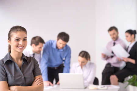 working: Business meeting - manager discussing work with his colleagues. woman standing on foreground with crossed hands and team on background