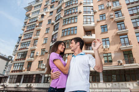 Couple in front of new home holding door keys and looking at each other. man hugging womam and holding apartment keys Stock fotó