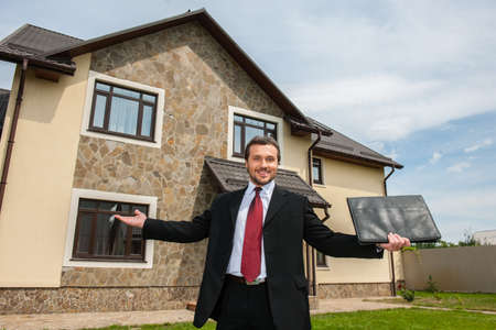 raised hands: smiling real estate agent ready to sell house. Male real etate agent in front of home raised hands