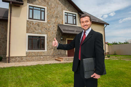 closeup on smiling real estate agent ready to sell house. Male real etate agent in front of home showing thumb up outside