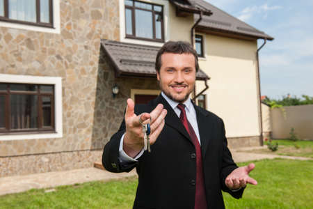 closeup on smiling real estate agent ready to sell house. Male real etate agent in front of home giving keys
