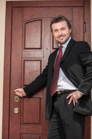 realtor opening wooden door and smiling. brown wooden door and business man in suit and tie