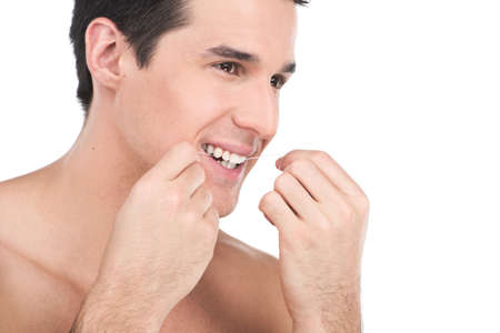 young man flossing his teeth isolated on white background. guy is flossing his teeth in front of bathroom mirror photo