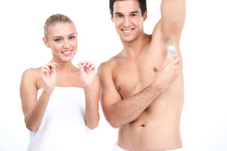 Young handsome man holding deodorant for armpits. beautiful woman standing on white background and holding floss