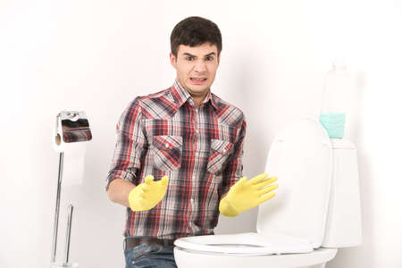 man cleaning toilet with spray cleaner. guy wearing gloves showing disgust near toilet seat photo