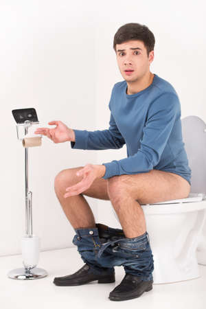 article of clothing: Young handsome man sitting on toilet. guy without toilet paper upset and made helpless gesture