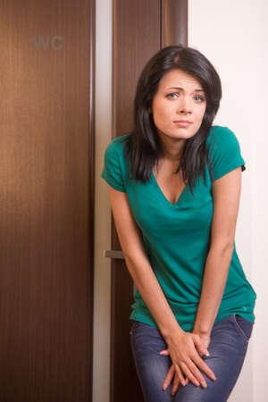 diarrea: hermosa chica morena de pie en la puerta del baño. bonita mujer de pelo negro quiere hacer pis