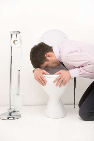 Man kneeling down in bathroom, vomiting into toilet. young guy standing over toilet seat with tie photo