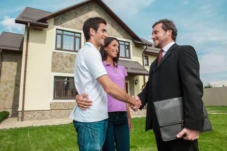 Salesman shaking hands with property owners. Handshake deal with young couple outside on lawn photo
