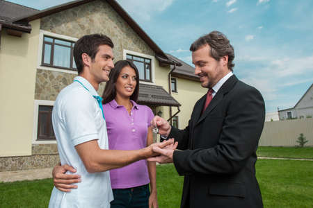 townhomes: Salesman giving keys to property owners. real estate agent signed deal with young couple outside Stock Photo