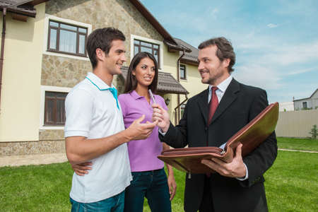 nieruchomosci: Młoda para podpisanie wynajem kontrakt z nieruchomościami. Środek podając pióro do podpisania umowy o sprzedaży domu Zdjęcie Seryjne