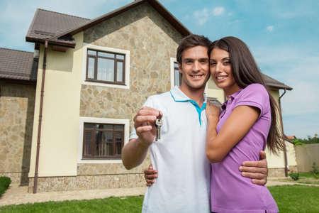 Paar voor nieuwe huis bedrijf deursleutels. Jong paar tonen hun nieuwe huissleutels