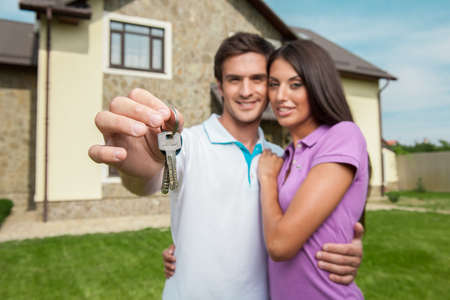 Couple in front of new home holding door keys. Closeup on man's hand showing new house keys