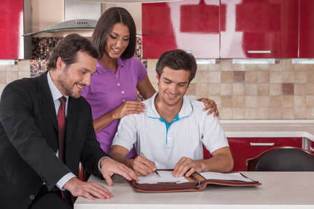 purchasers: happy man signing agreement on new house. young couple purchasing new kitchen