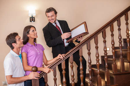 Estate agent with young couple on ladder. three going up to second floor on wooden ladder to see house photo