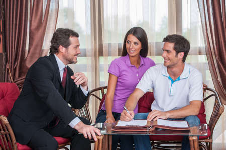 closeup on happy man signing agreement on new house. agent looking at young couple purchasing new house
