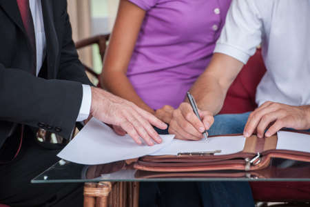 closeup on happy man hand signing agreement on new house. agent giving documents to young couple purchasing new house