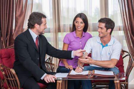 closeup on happy man taking keys to new house. agent giving keys to young couple purchasing new house