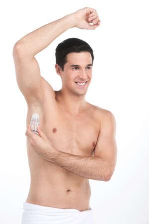 axila: Hombres guapos j�venes aplicaci�n de desodorante en las axilas. hombre desnudo de pie sobre fondo blanco y sonriente