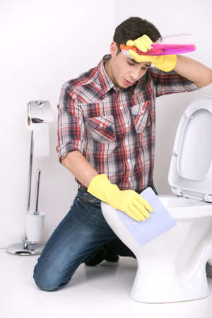 anti bacterial soap: man cleaning toilet with spray cleaner. tired guy wiping forehead from sweat in bathroom