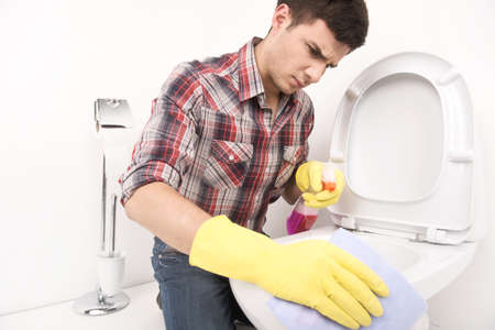 man cleaning toilet with spray cleaner. disappointed guy wiping toilet seat in bathroom Stock Photo