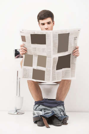 Young handsome man sitting on toilet and reading magazine. guy reading articles and stories in newspaper while in loo