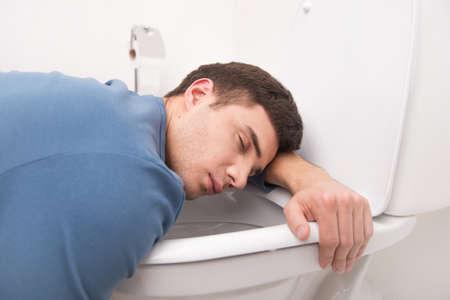 young man lying on toilet seat. guy kneeling over toilet seat and sleeping photo