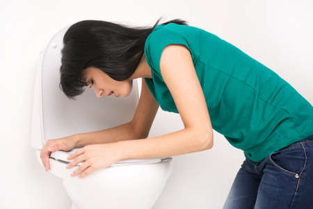 Young caucasian woman in toilet - pregnant, drunk or illness concept. Young dark-haired woman vomiting in toilet photo
