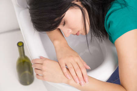 Young caucasian woman in toilet - drunk concept. Young dark-haired woman vomiting in toilet photo
