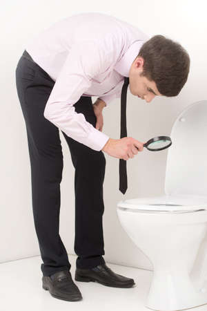 loo: young business man with magnifying glass. guy looking at toilet seat through magnifying glass Stock Photo