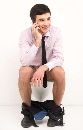 a toilet seat: Man with mobile phone sitting on toilet. Businessman talking on phone while sitting on toilet