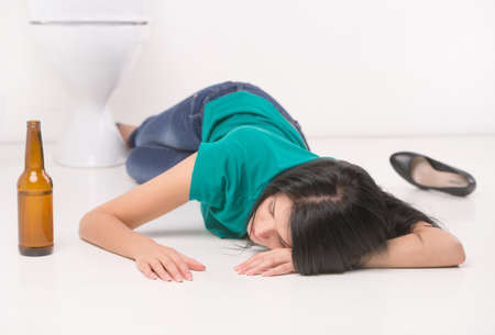 intoxicated: Drunk woman lying on toilet floor. black-haired girl sleeping on toilet tile with bottle