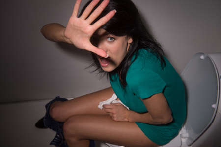 Portrait of young woman shouting in toilet to camera. top view of scared black-haired girl lifted hands and hiding from camera Stock Photo