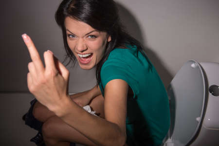 fuck: Portrait of young woman shouting in toilet to camera. top view of upset and angry black-haired girl showing midle finger sign