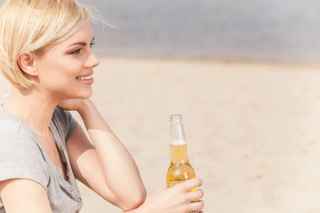 nonalcoholic beer: Woman sitting on beach and drinking beer. summer holidays and vacation spent on lake shore