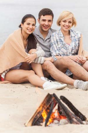 under fire: tres amigos sentados bajo la manta y calentamiento cerca el fuego