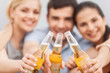 Man en twee vrouwen ontspannen op het strand met bier.