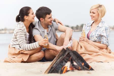 under fire: amigos felices que se divierten alrededor hoguera. tres amigos sentados bajo la manta y calentamiento cerca el fuego