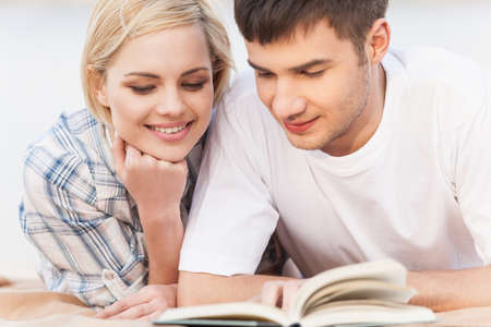 Portrait Of Happy Couple Reading Book On Summer Beach. Couple reading book on lake shore
