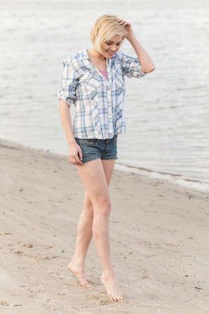 blond girl walking along lake shore.