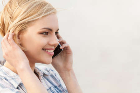pretty blond talking on cellphone and smiling. closeup on happy beautiful girl face with phone Stock fotó