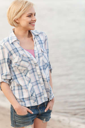 Young woman in shirt and jeans standing on sea shore.