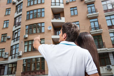 couple standing with their backs towards camera. man pointing to apartment window for brunette woman