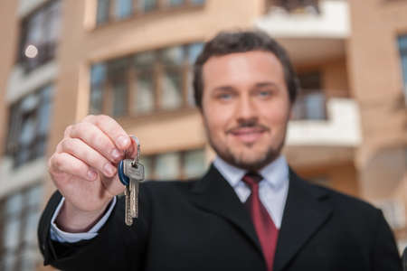 closeup on adult man holding key to dream house with building on background. real estate agent looking into camera and giving keys to apartment