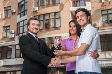 townhomes: Salesman giving keys to property owners. Stock Photo